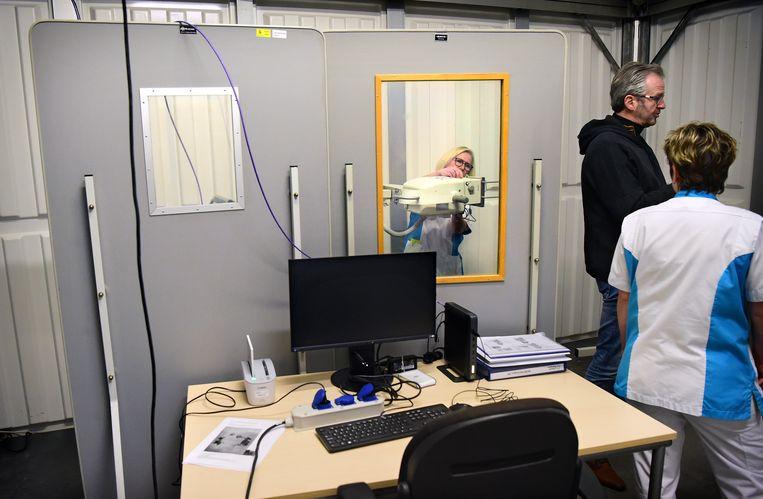 Achter het raam wordt de CT-scanner in gereedheid gebracht in het Udense ziekenhuis Bernhoven, dat zich alleen nog richt op coronapatiënten. Beeld Marcel van den Bergh / de Volkskrant