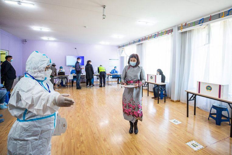 Woensdag waren er verkiezingen in Mongolië. Ambtenaren die moesten toezien op het stemproces dragen beschermende kleding. Beeld AFP