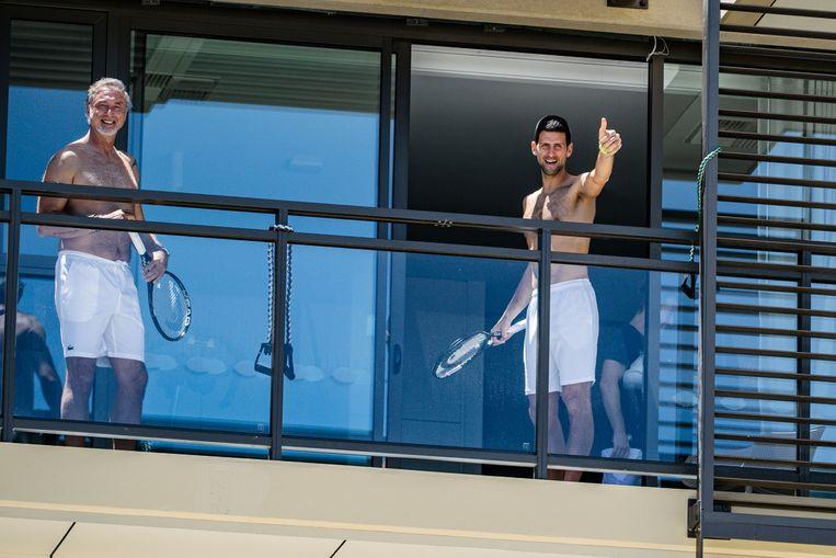 Novak Djokovic zwaait vanuit zijn hotelkamer in Adelaide, een van de twee locaties waar tennissers zich voorbereiden op de Australian Open in Melbourne. De speler uit Servië testte in juni 2020 al positief op corona. Beeld AFP
