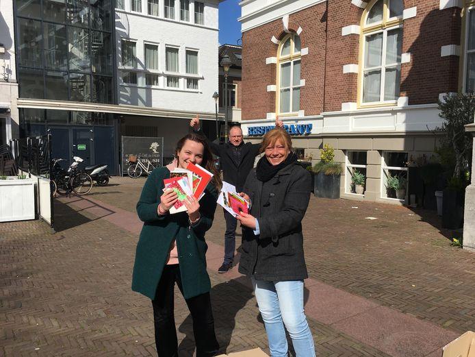Leanne Enderink en Bianca Ladage (r) tonen een paar van de kaarten die passanten hebben geschreven. Burgemeester Ton Heerts (achter) maakt duidelijk dat hij hun initiatief top vindt.
