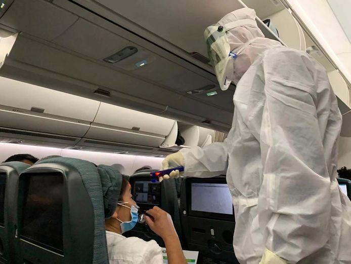 Een gezondheidsmedewerker neemt de temperatuur op bij een passagier van een Cathay Pacific-vlucht.