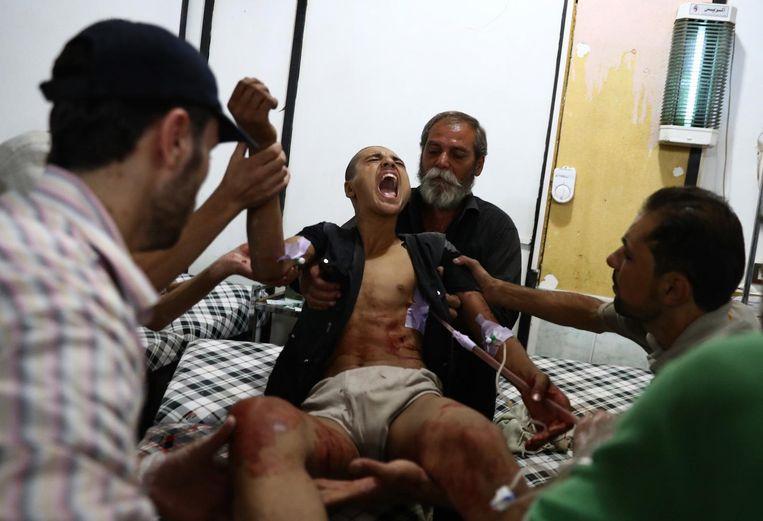 Een gewonde man in een ziekenhuis in Douma, nabij Damascus, waar vlak voor het bestand inging nog werd gevochten. Beeld afp
