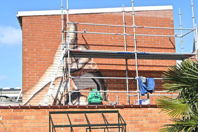 Grafitti-artieste Jonk. maakt een mural die zichtbaar is van in de Hemelstraat.