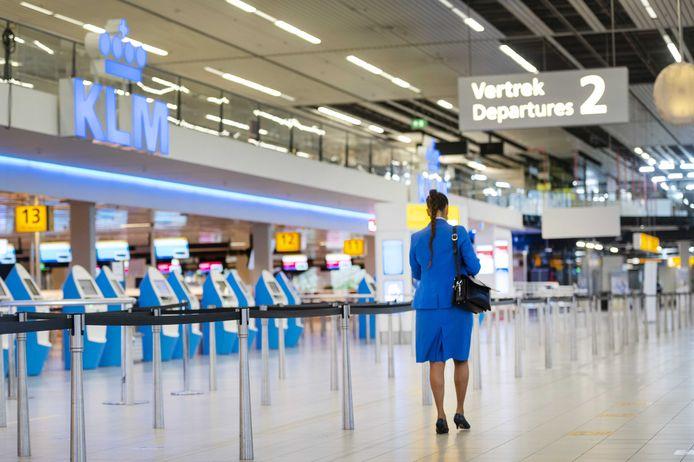 Een KLM stewardess op luchthaven Schiphol