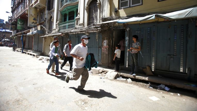 Een Nepalese man rent de straat op in Kathmandu, na een nieuwe aardbeving. Beeld ap