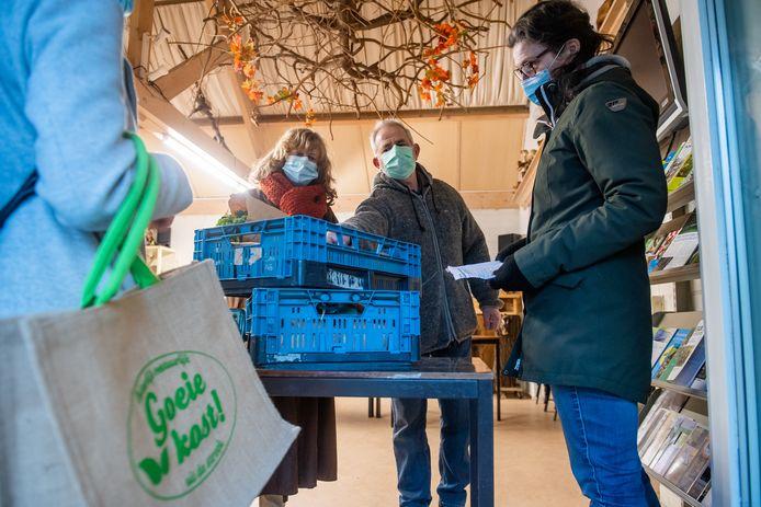 Made - Pix4Profs/René Schotanus. Een klant komt een krat ophalen bij vlnr Riny en René Muller en Edith Verkooijen.