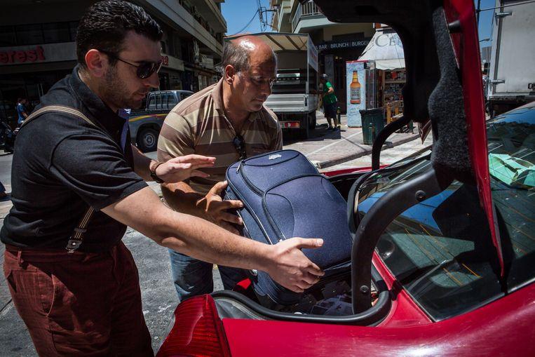 Abu Saif laadt zijn koffer in in de achterbak van de taxi die hem naar het kamp brengt. Beeld Cigdem Yuksel