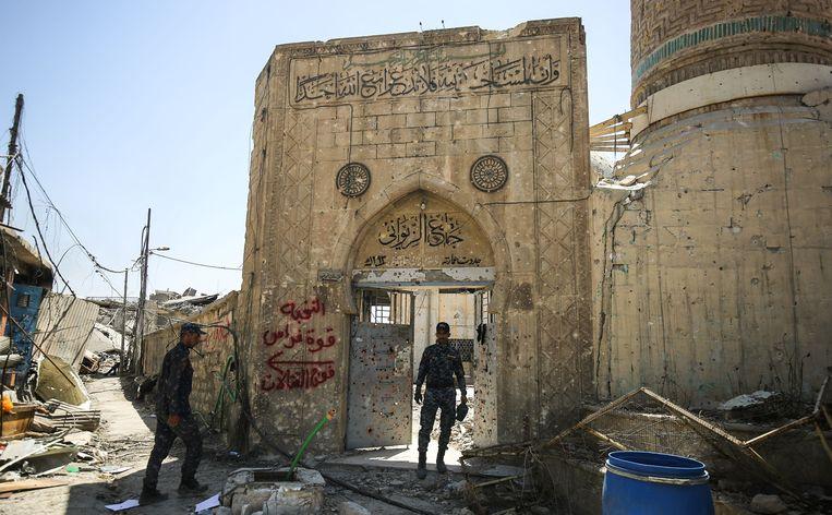 ► Een lid van de Iraakse federale politie staat in het deurgat van het heroverde symbolische heiligdom Al-Nuri. Beeld AFP