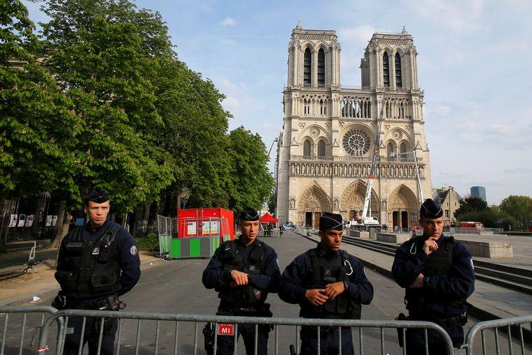 Politieagenten bewaken het plein rond de Notre-Dame. Beeld REUTERS