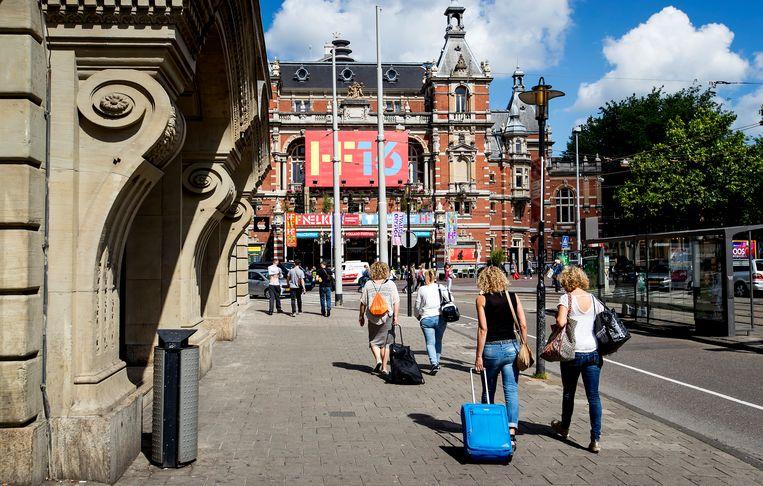 Toeristen met rolkoffers op het Leidseplein in Amsterdam.  Beeld null