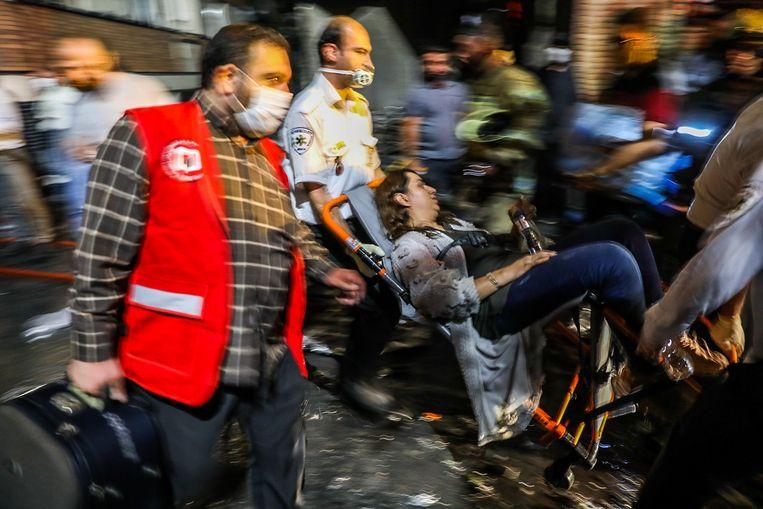 Een vrouw wordt in een rolstoel weggedragen na een explosie in een ziekenhuis in Teheran.  Beeld AFP