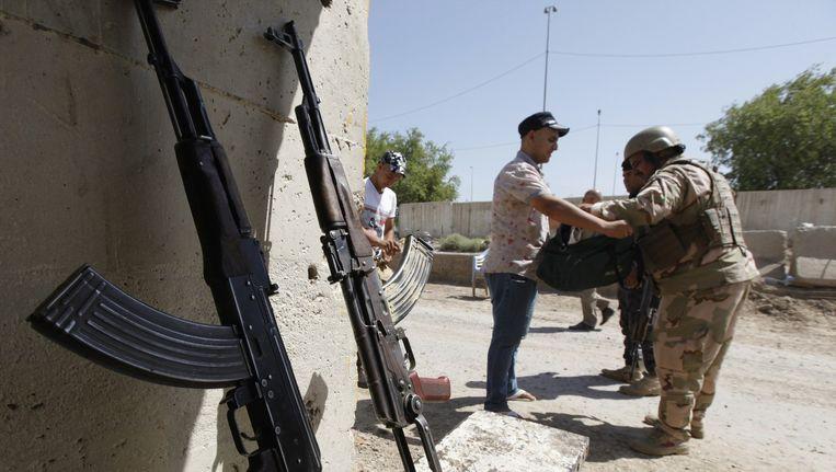 Iraakse soldaten fouilleren een vrijwilliger die zich heeft gemeld voor de strijd tegen ISIS. Beeld reuters
