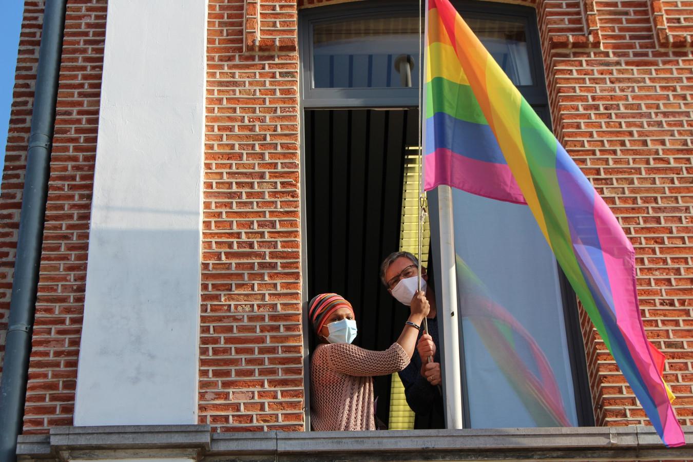Schepen van Welzijn Sumati Adriaensen en burgermeester Ward Kennes hangen de regenboogvlag op aan het gemeentehuis in Kasterlee