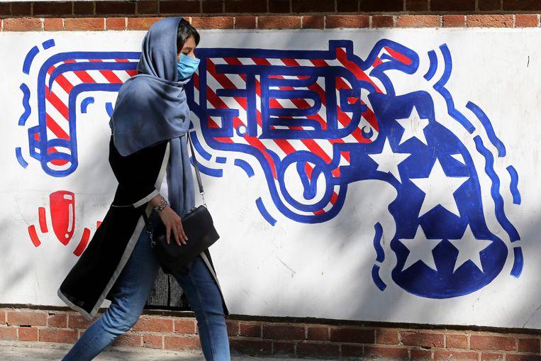 Een vrouw wandelt langs graffiti op de muur van de voormalige Amerikaanse ambassade in de Iraanse hoofdstad Teheran.  Beeld AFP