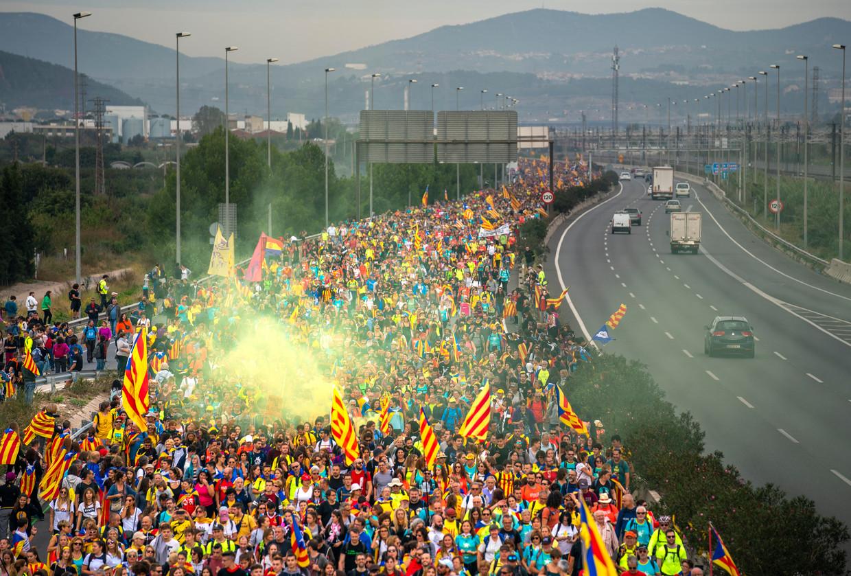 Catalanen lopen over de snelweg naar de Spaanse stad Barcelona in protest tegen de veroordeelde Catalaanse leiders. Beeld Freek van den Bergh