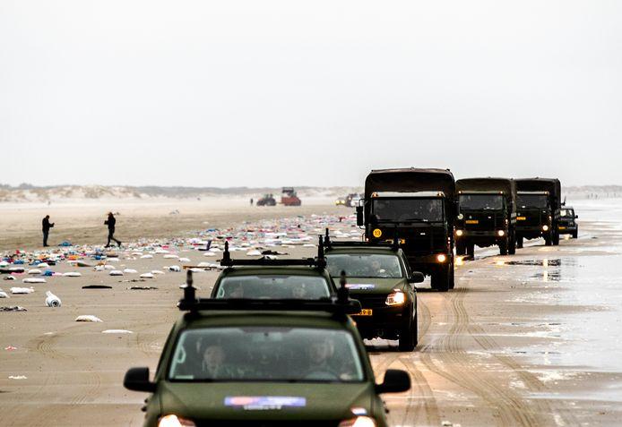 Militairen ruimen de spullen op die op het strand van Schiermonnikoog zijn aangespoeld.