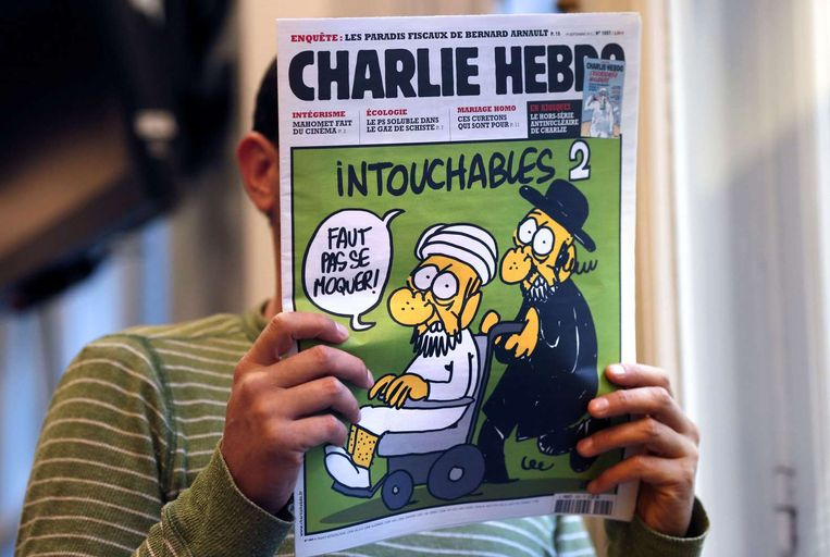 Een man in Parijs leest een nummer van Charlie Hebdo uit september 2012 Beeld afp