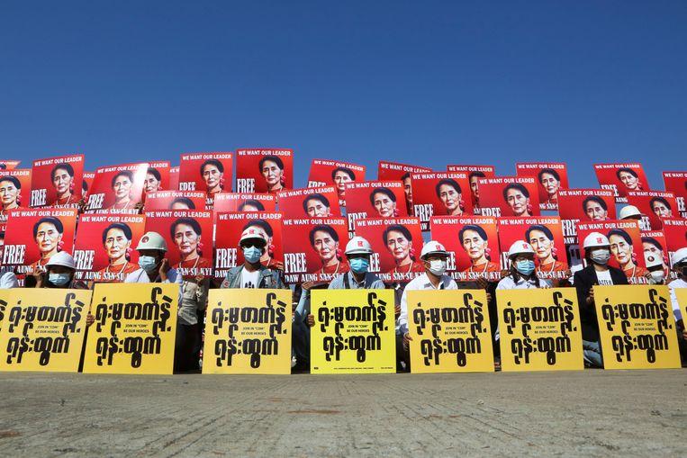 Demonstranten houden een bord omhoog waarop ze de vrijlating eisen van de gearresteerde regeringsleider Aung San Suu Kyi.  Beeld REUTERS