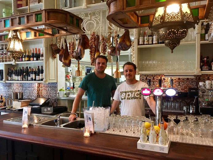 Eigenaar Arris Boogaard (l) en chef-kok Roel van Druten achter de bar bij El Patio in Breda. De Spaanse hammen hangen al klaar. Vanaf komende weekend zal de bar ook vol staan met pintxos.