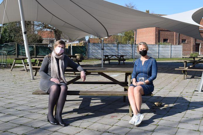 Schepen van onderwijs Isabel Dellaert (Vooruit) en directrice Ann Lecluyse op de picknickbank onder de nieuwe shelter op de grote speelplaats.