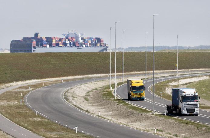 Een containerschip vaart de Rotterdamse haven in. Op de voorgrond vrachtverkeer op de Maasvlakte.