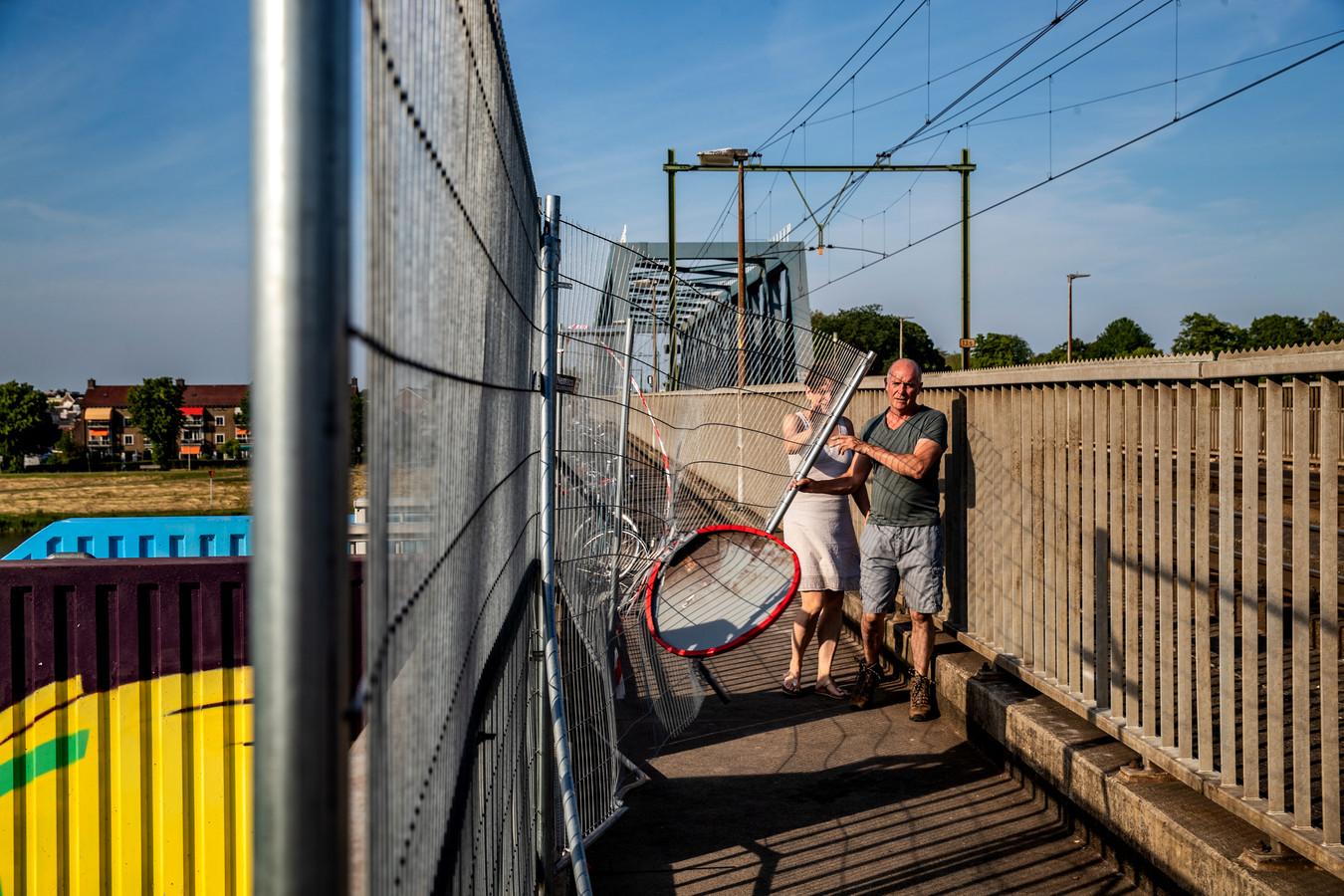 Kieran Behan kruipt behendig langs het opengevouwen hek op de spoorbrug. Het zou jongeren de weg naar de landtong moeten versperren. Veel effect heeft het alleen niet.
