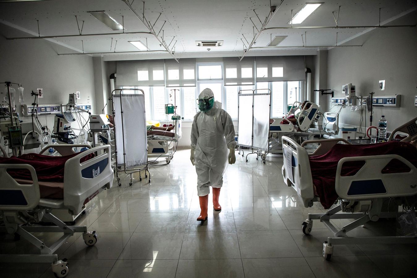 Un membre du personnel médical contrôle des patients atteints du coronavirus Covid-19 dans le service de soins intensifs d'un hôpital à Bogor, le 18 juin 2021, alors que le taux d'infection par le coronavirus Covid-19 monte en flèche en Indonésie.