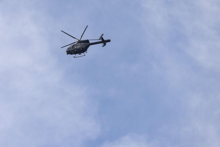 Een politiehelikopter hangt boven het een bos nabij Dilsen-Stokkem waar C. zich mogelijk verschanst heeft. Beeld BELGA