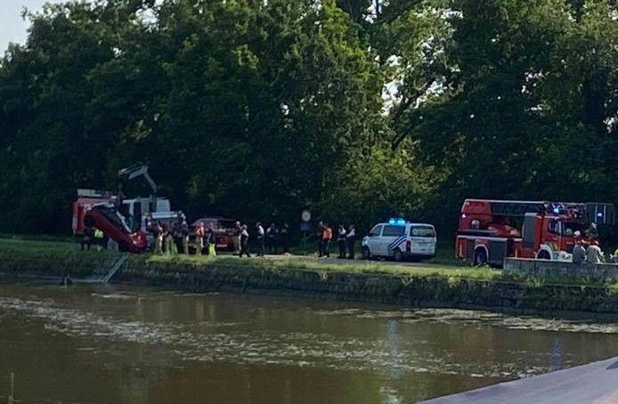 De auto wordt door de hulpdiensten uit het kanaal gehesen.