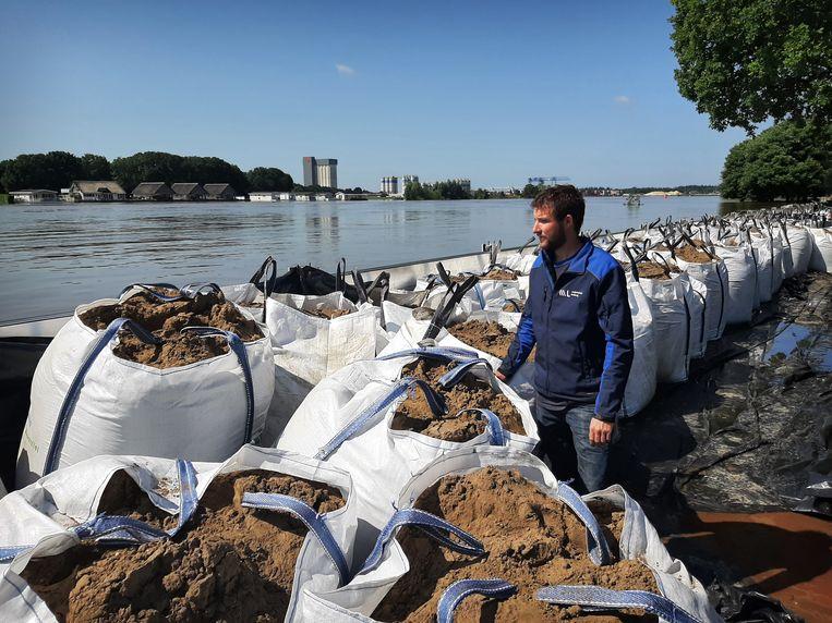 Ivo van Enckevort, inspecteur van Waterschap Limburg, bekijkt de situatie aan de kade in Well. Daar zijn een demontabele kering en big bags met zand geplaatst.  Beeld Ellen van Gaalen