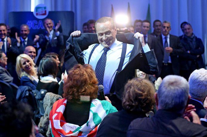 Silvio Berlusconi  doet zijn jas uit om zijn borstspieren te laten zien.