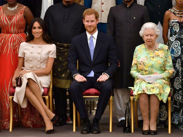 Queen Elizabeth met haar kleinzoon Harry en diens vrouw Meghan. Beeld REUTERS