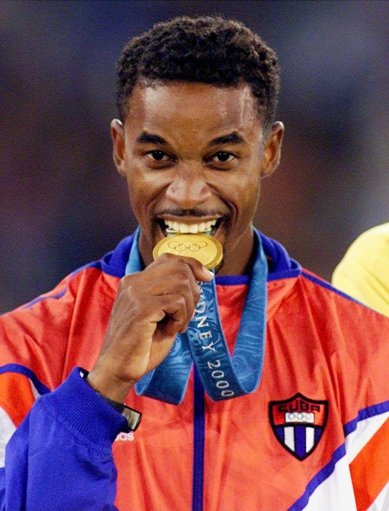 Cuba's Ivan Pedroso bijt op zijn gouden medaille die hij won op de Olympische spelen van Syney in 2000. Beeld ap