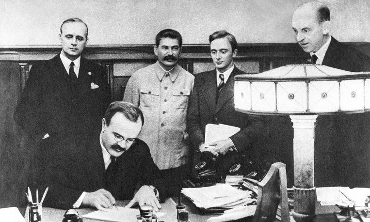 Sovjet-minister van Buitenlandse Zaken Vjatsjeslav Molotov tekent het niet-aanvalsverdrag tussen nazi-Duitsland en de Sovjet-Unie in 1938. Achter hem kijken zijn Duitse collega Joachim von Ribbentrop (links) en Sovjetleider Jozef Stalin (met snor) toe.  Beeld TASS via Getty Images