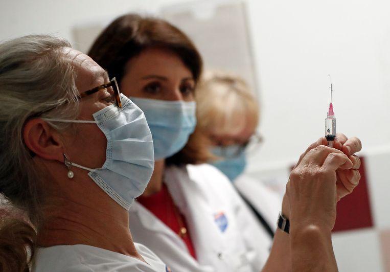 Een zuster in Frankrijk bereidt een dosis vasn het Pfizer-BioNTech coronavaccin voor. Per september zijn  alle zorgmedewerkers in Frankrijk verplicht om zich te laten vaccineren.  Beeld EPA
