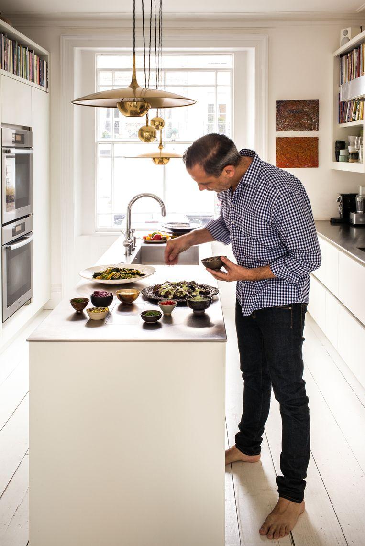 Ottolenghi aan het werk in zijn keuken. Zijn dessertboekenverzameling verraadt zijn opleiding als patisseriechef.   Beeld Paul Raeside
