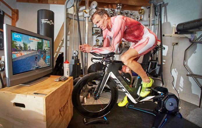 Ron van der Pol uit Maren-Kessel hoopt een triathlon te volbrengen.  Op de foto in zijn schuur op de hometrainer.