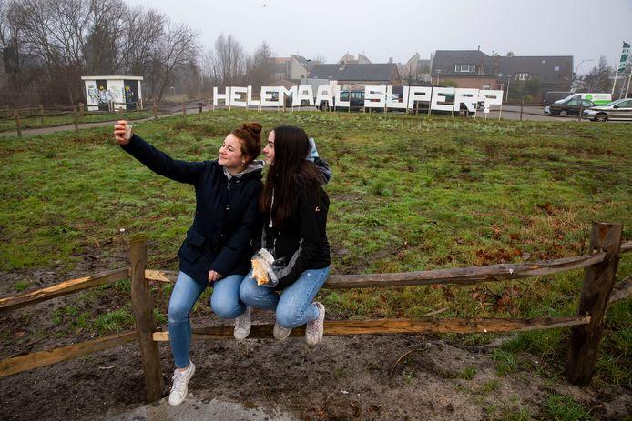 Kim en Alec nemen een selfie bij de tekst 'Helemaal Super?', een verwijzing naar de nieuwe plannen voor het centrum.