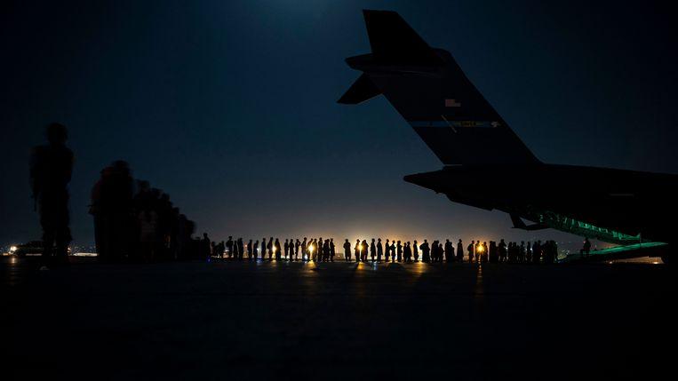 Op het vliegveld van Kabul verdringen Afghanen zich om een vlucht te bemachtigen. Beeld AFP