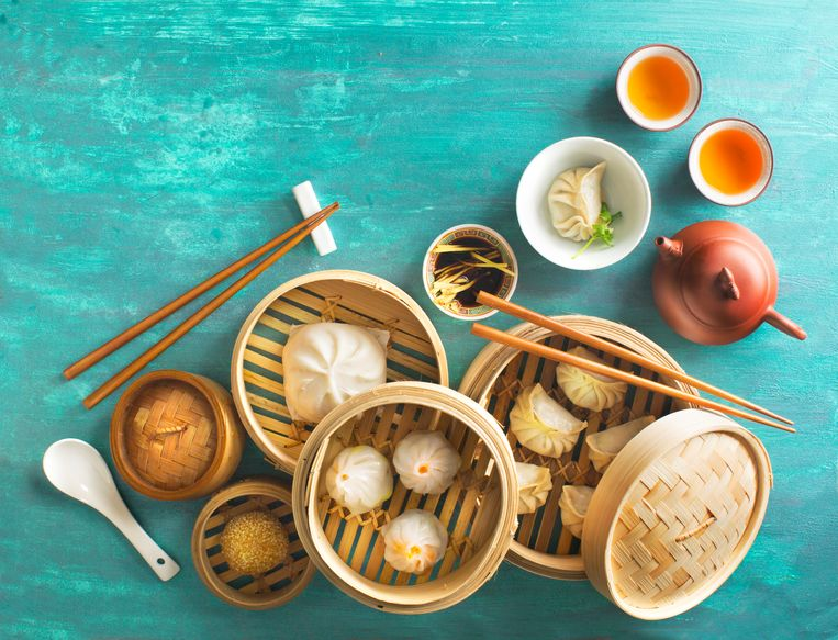 Assorted Chinese food dim sum, steamed bun, dumpling and traditional tea set on green textured table top. Flat lay overhead view text space image. Beeld Getty Images