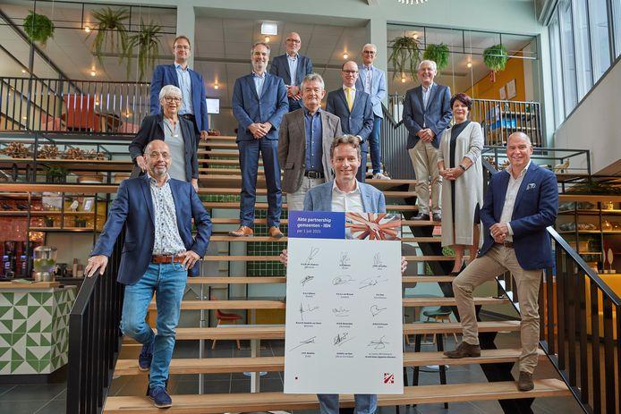 De elf wethouders en de algemeen directeur van IBN op de trap bij het sociaal ontwikkelbedrijf in Uden.