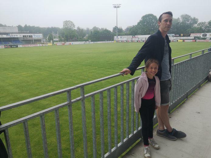 Roel Grant met dochter Stella op de tribune. In de hoek van het veld staat het scorebord.