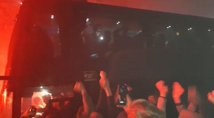 De spelers in de bus zwaaien naar de fans en maken opnames met hun mobieltjes van het feestgedruis.