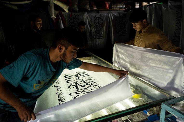 In een kleine werkplaats in Kaboel worden Talibanvlaggen geprint. De vlaggenwinkel, verscholen op de binnenplaats van de Kaboelmarkt, documenteerde Afghanistans turbulente geschiedenis door de jaren heen. Nu ligt de winkel vol met zwart-witte Talibanvlaggen, versierd met de Islamitische geloofsbelijdenis uit de Koran. Beeld AP