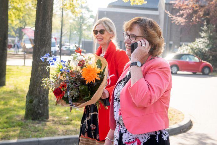 Burgemeester Anneke Raven (aan de telefoon) op weg naar een inwoner die een koninklijke onderscheiding kreeg.