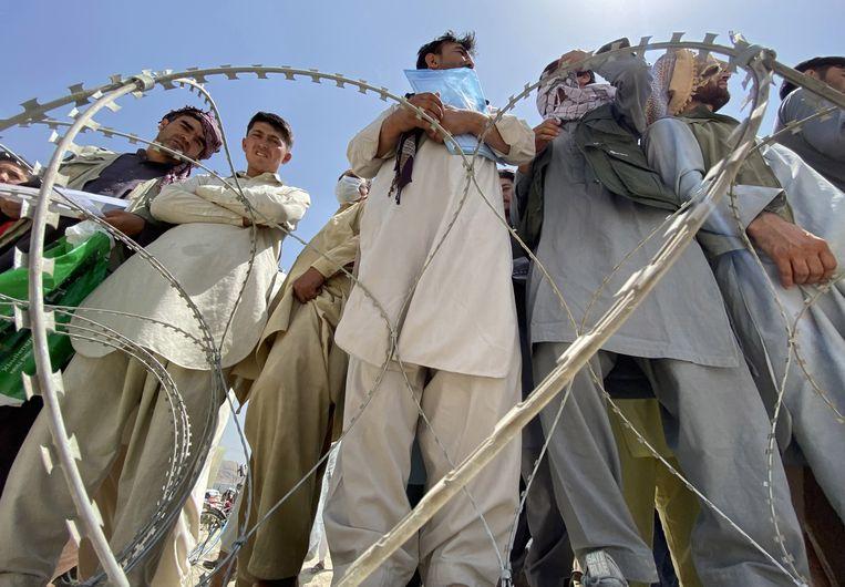 Afghanen wachten op het vliegveld in Kaboel op een vlucht het land uit. Velen van hen hebben de westerse troepen geholpen als tolk of klusjesman, en dreigen daar nu een zware prijs voor te betalen. Beeld EPA