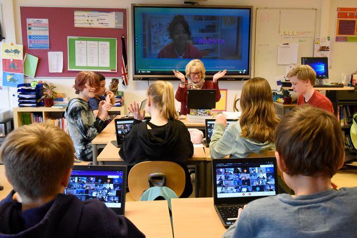 Juf Corine Schaap van basisschool De Regenboog in Woerden geeft het grootste deel van haar groep 8b online les, terwijl er ook een aantal leerlingen in de klas zitten omdat zij in aanmerking komen voor noodopvang.