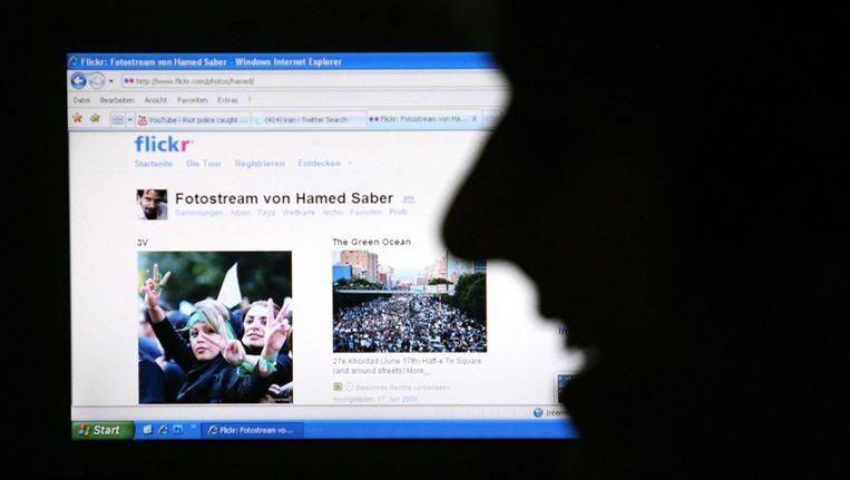 Een man in Duitsland volgt nieuws via Flickr over Iran. Beeld EPA