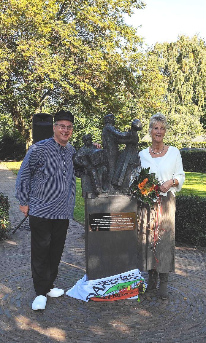 Voorzitter Gerrit Mollink van de Folkloristische Dansgroep Hellendoorn en cultuurwethouder Anja van den Dolder bij het beeldje, waarop de plaquette is aangebracht.