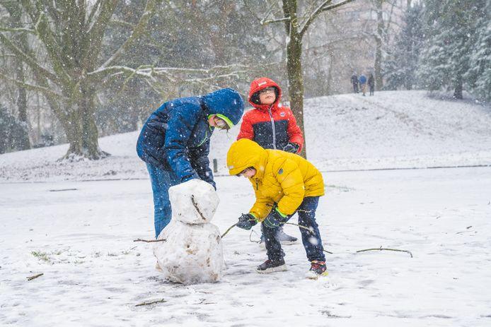 Een sneeuwman met takken van de bomen, bij gebrek aan bezemsteel.